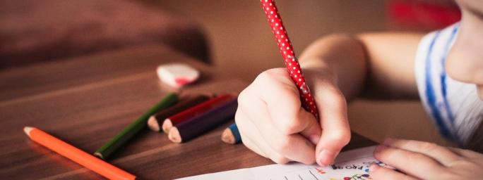 Malá holčička s tužkou v ruce píše do sešitu
